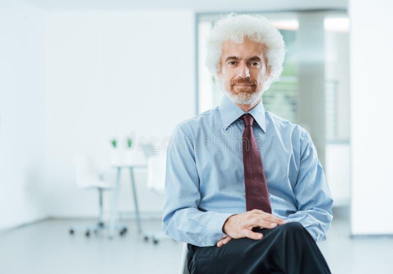 Überzeugter Geschäftsmann, der im Büro aufwirft lizenzfreies stockbild