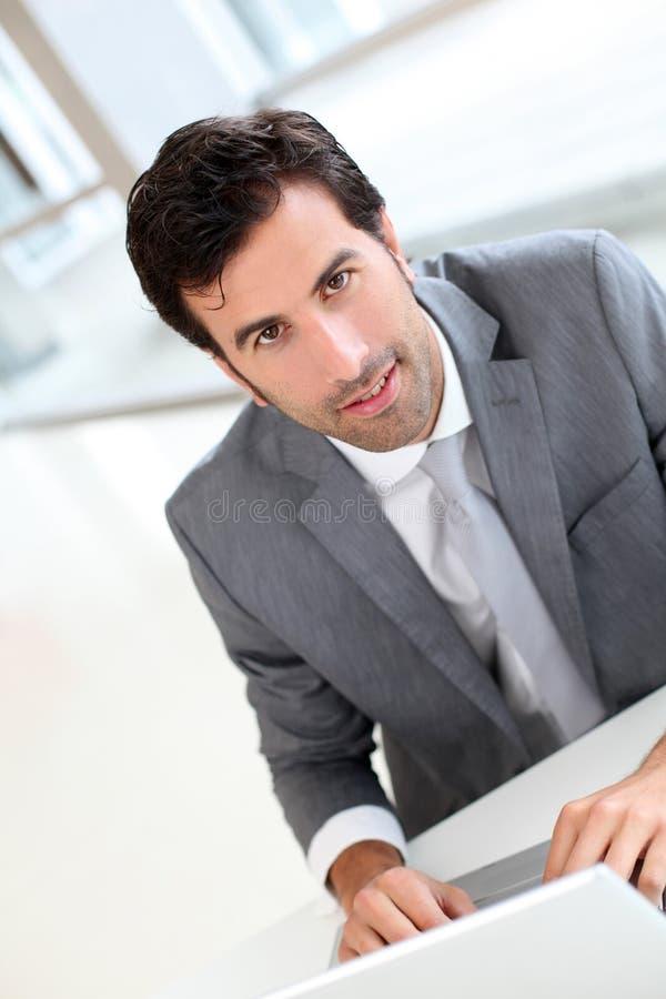 Überzeugter Geschäftsmann, der im Büro sitzt stockfotos