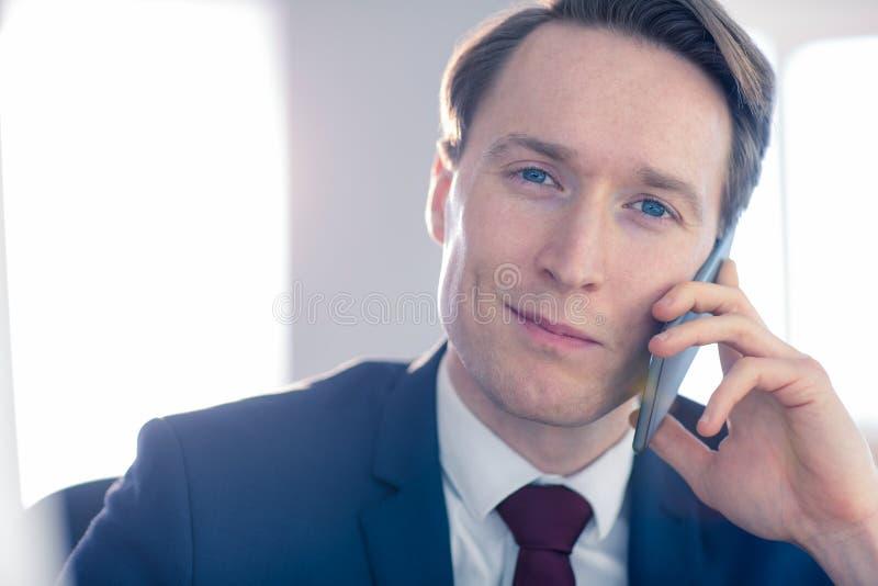 Überzeugter Geschäftsmann, der Kamera beim Haben eines Telefonanrufs betrachtet lizenzfreie stockfotos