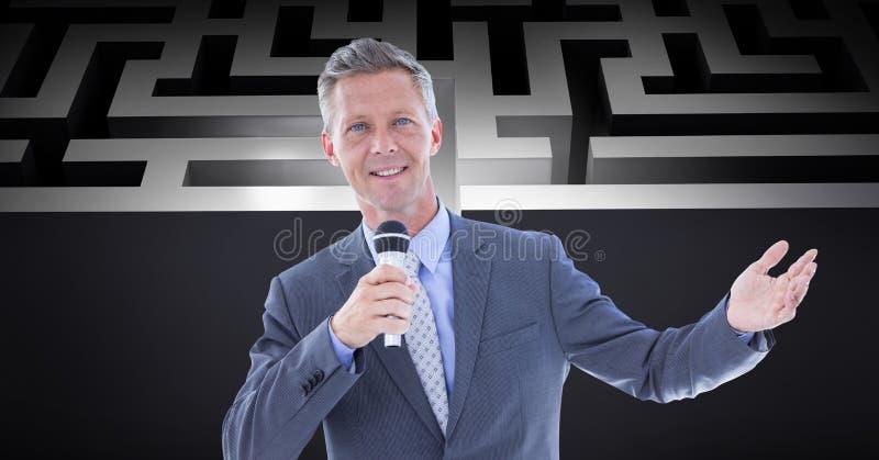 Überzeugter Geschäftsmann, der Mikrofon gegen Labyrinth hält stockbilder