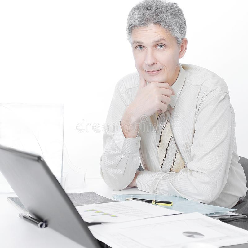 Überzeugter Geschäftsmann, der an seinem Arbeitsplatz im Büro sitzt lizenzfreie stockfotos