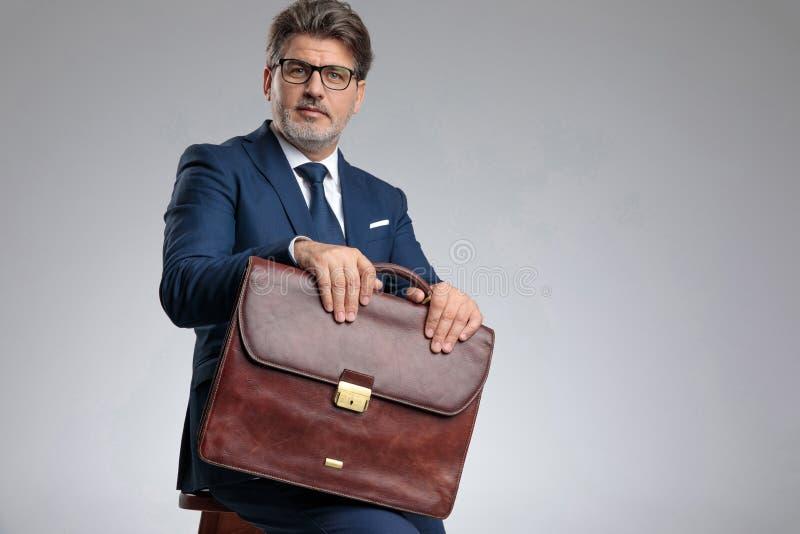 Überzeugter Geschäftsmann, der seinen Aktenkoffer beim Sitzen hält stockfoto
