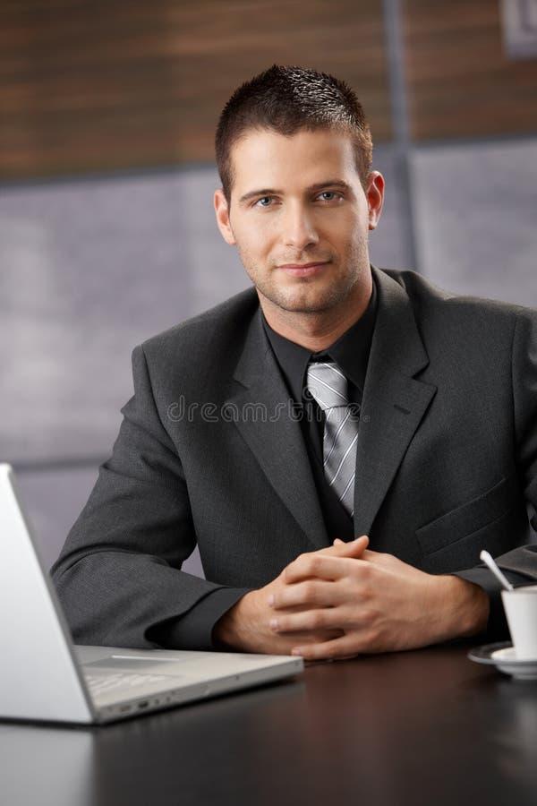 Überzeugter Geschäftsmann, der am Versammlungstisch sitzt lizenzfreie stockfotografie