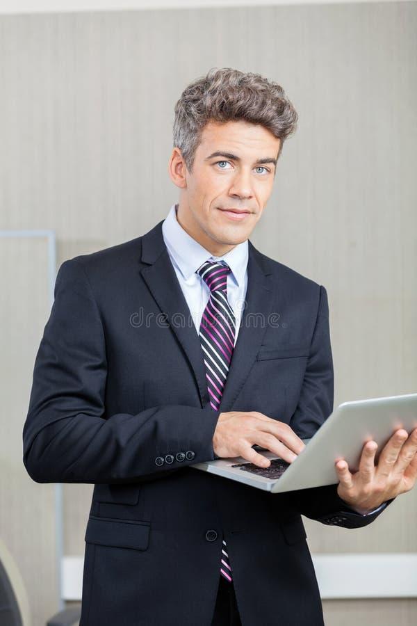 Überzeugter Geschäftsmann mit Laptop stockfotos