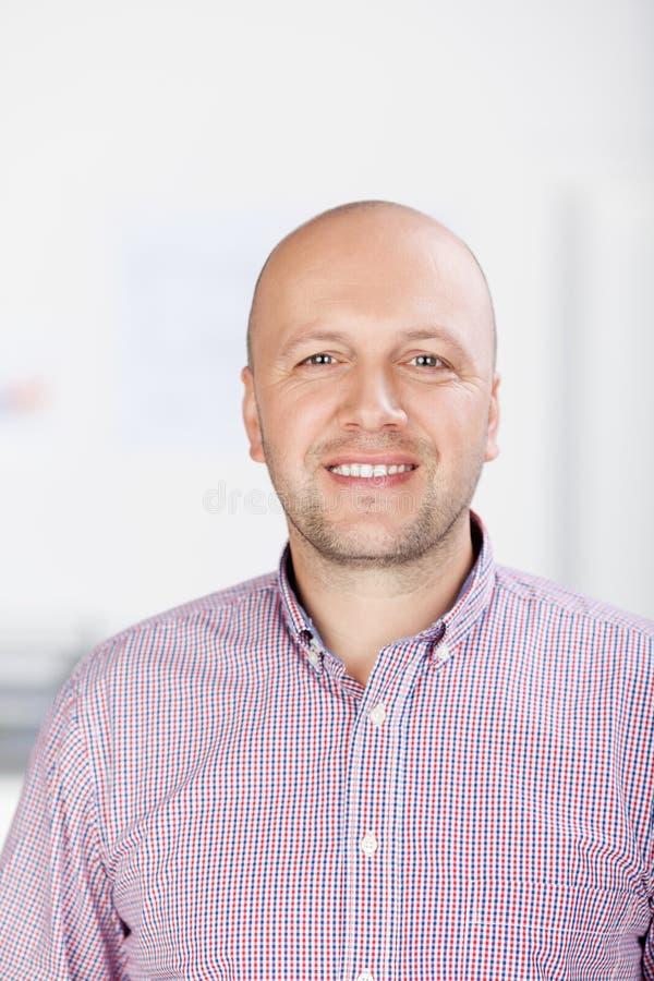 Überzeugter Geschäftsmann Smiling In Office lizenzfreie stockfotografie
