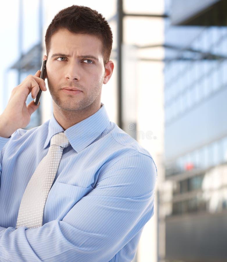 Überzeugter Geschäftsmann unter Verwendung des Mobiles draußen lizenzfreies stockfoto