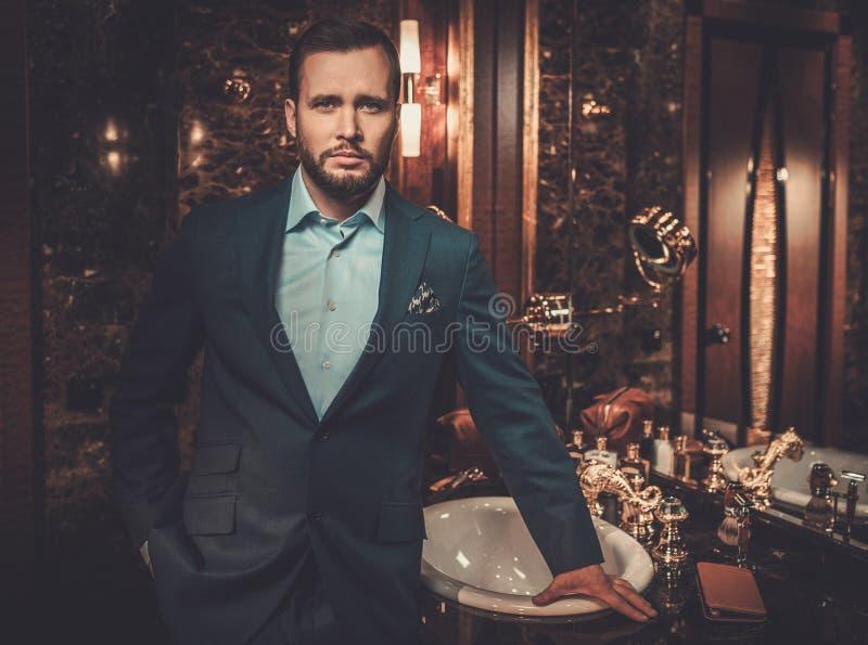 Überzeugter gut gekleidet Mann im Luxusbadezimmerinnenraum stockfotos