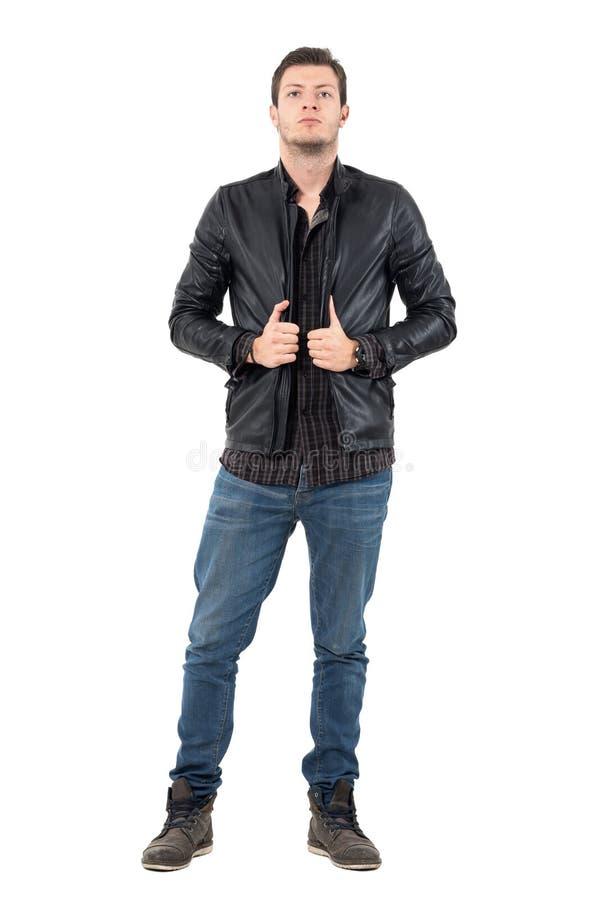 Überzeugter gutaussehender Mann, der in der schwarzen Lederjacke betrachtet Kamera aufwirft lizenzfreie stockfotografie