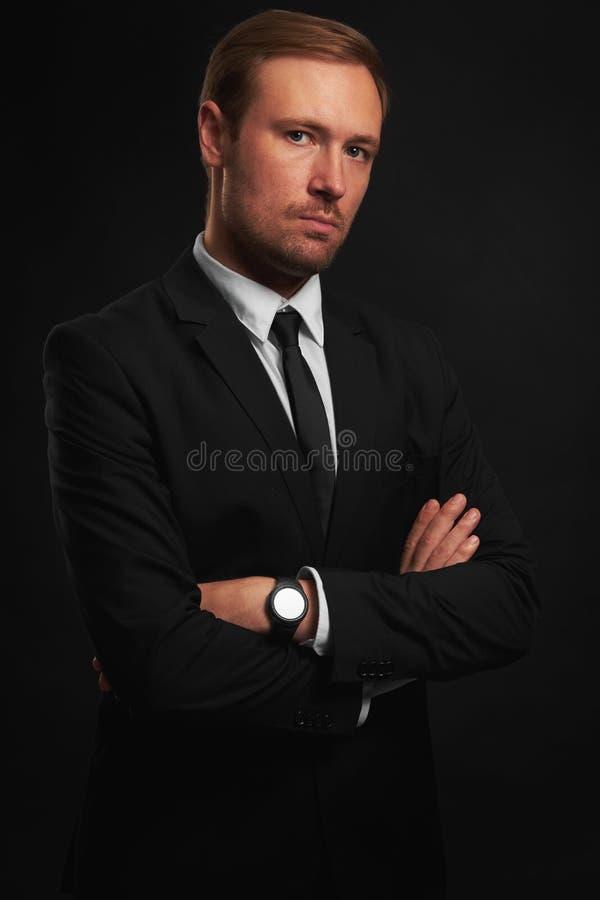 Überzeugter gutaussehender Mann im schwarzen Anzug lizenzfreie stockfotos