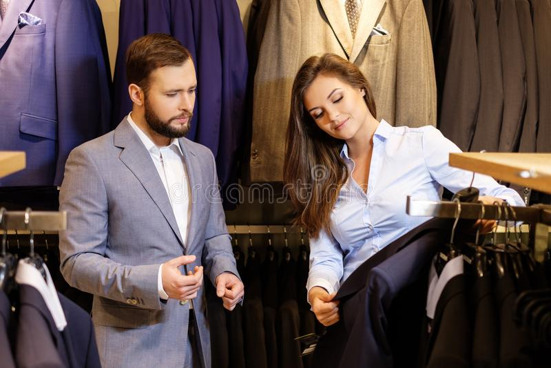 Überzeugter gutaussehender Mann mit dem Bart, der eine Jacke in einem Anzugsshop wählt lizenzfreie stockbilder