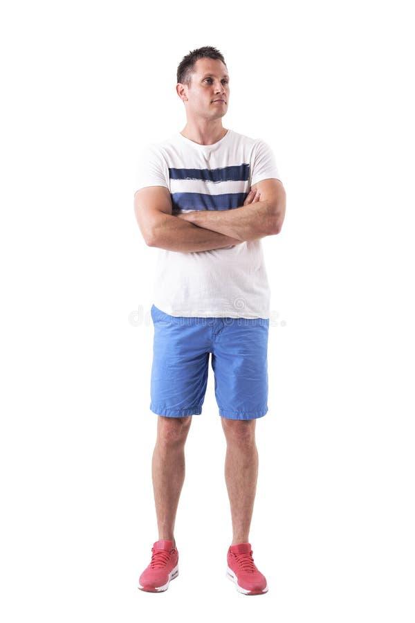 Überzeugter hübscher junger erwachsener muskulöser Mann, der oben schaut, aufwerfend mit den gekreuzten Armen stockfotografie