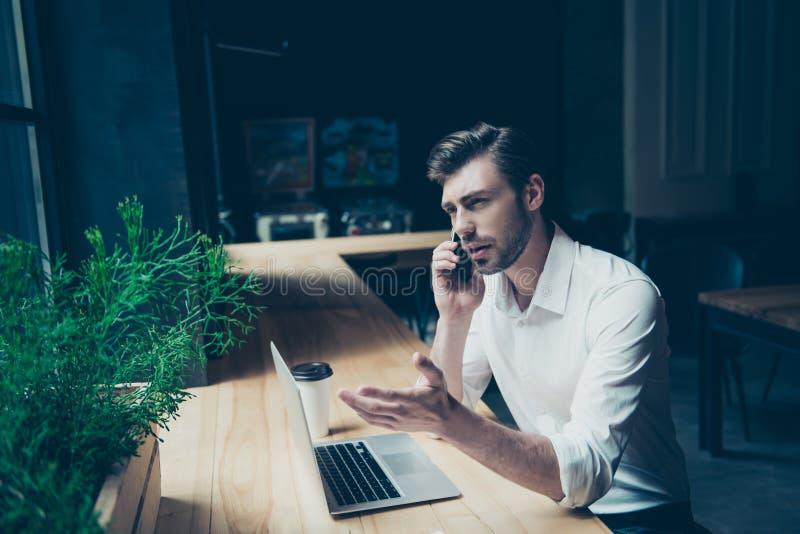 Überzeugter hübscher junger Mann hat ein Geschäftsgespräch, stockfotos