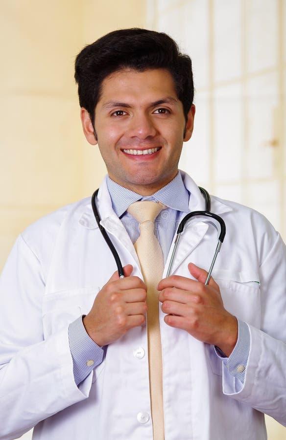 Überzeugter hübscher lächelnder Doktor, der Kamera mit einem Stethoskop um seinen Hals, im Bürohintergrund aufwirft und betrachte stockbild