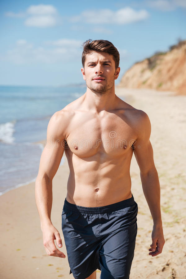 Überzeugter hemdloser junger Mann, der entlang den Strand geht stockbild