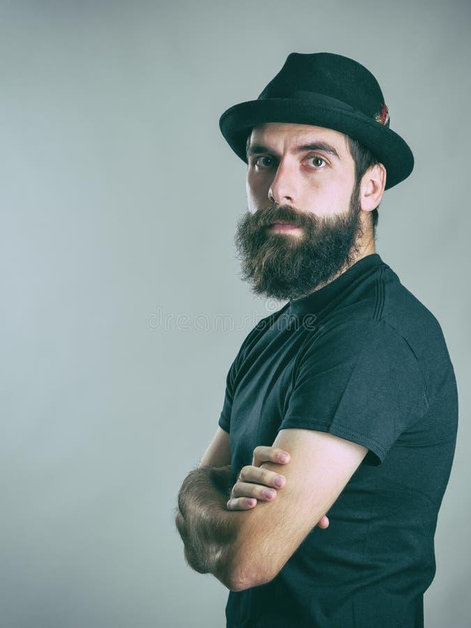 Überzeugter Hippie, der schwarzen Hut und das T-Shirt betrachtet Kamera mit den gekreuzten Armen trägt stockbild