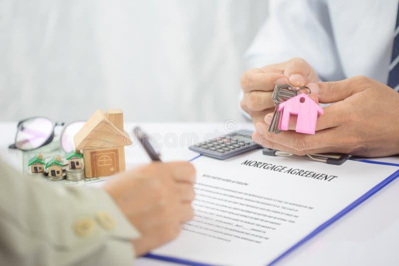 Überzeugter Holding-Hausschlüssel des jungen Mannes Hand, Immobilienagentur stockfoto