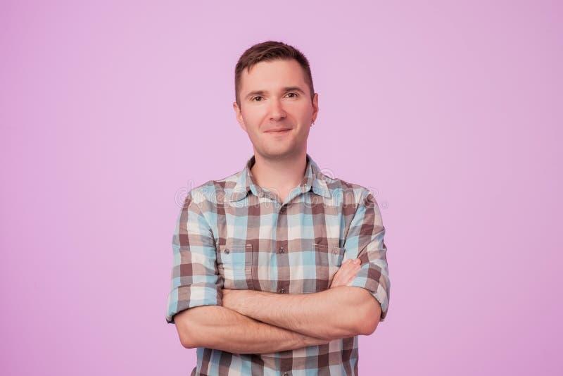 Überzeugter junger Arme haltener und bei der Stellung lächelnder gutaussehender Mann gekreuzt gegen rosa Hintergrund stockbilder