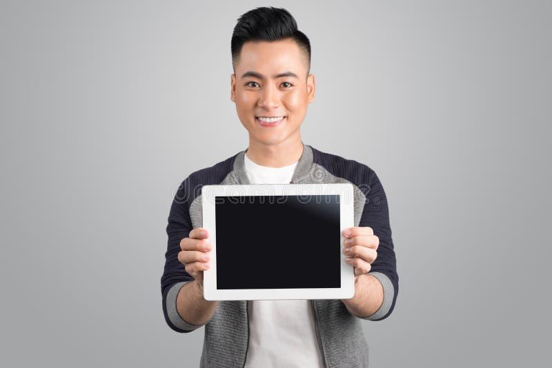 Überzeugter junger asiatischer Geschäftsmann, der digitalen Tablettenschirm zeigt lizenzfreie stockfotografie