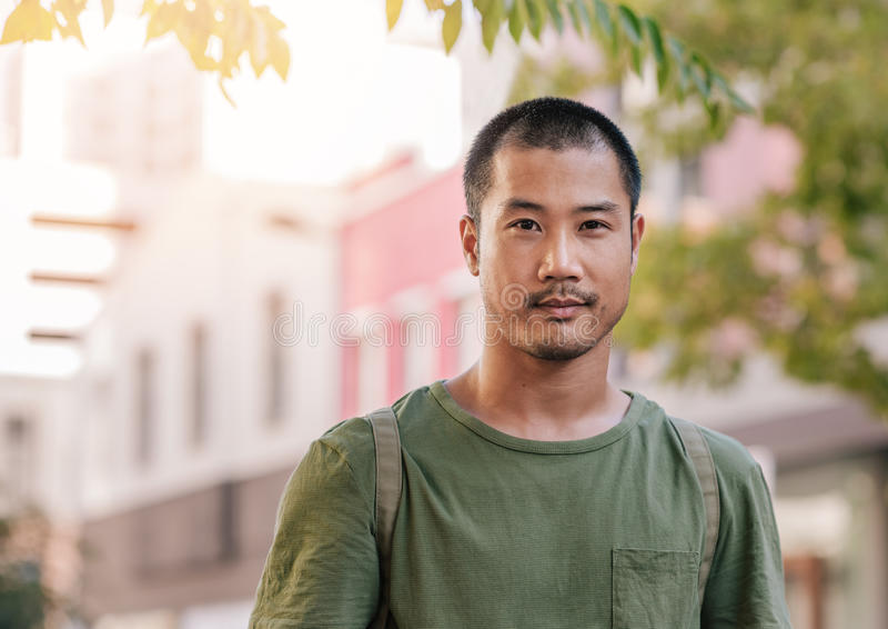 Überzeugter junger asiatischer Mann, der auf einer Stadtstraße steht lizenzfreie stockbilder