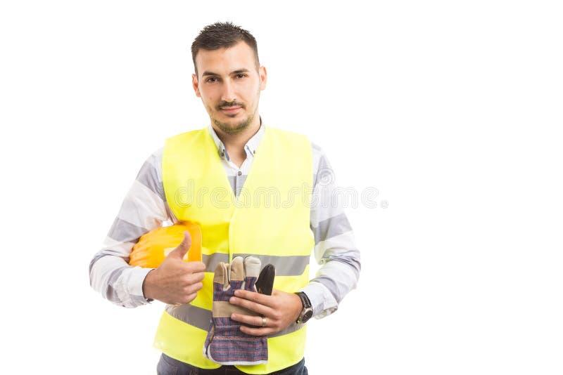 Überzeugter junger Bauunternehmer, der thumbsup zeigt lizenzfreie stockfotos