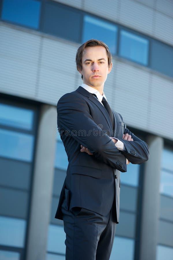 Überzeugter junger Geschäftsmann, der draußen mit den Armen gekreuzt steht lizenzfreies stockbild