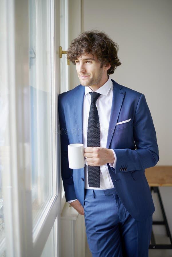 Überzeugter junger Geschäftsmann mit seinem Morgenkaffee stockfoto