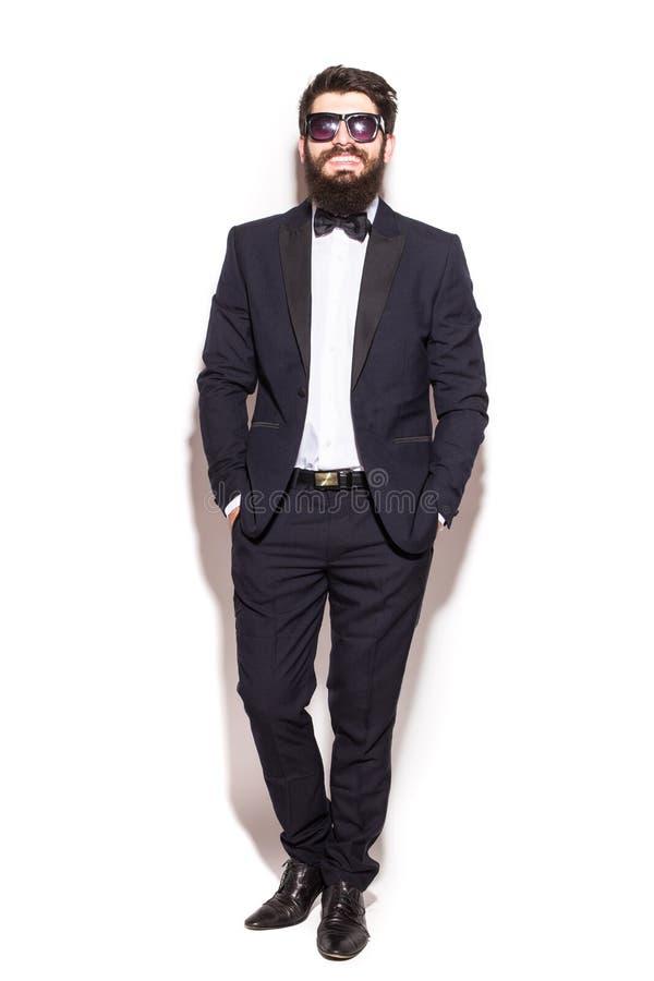 Überzeugter junger gutaussehender Mann der vollen Höhe im Sonnenbrillehändchenhalten in den Taschen und Betrachten der Kamera stockfoto