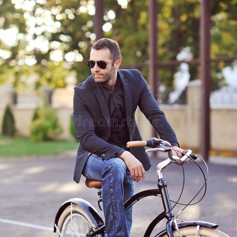 Überzeugter junger Mann auf einem Weinlesefahrrad stockfotografie