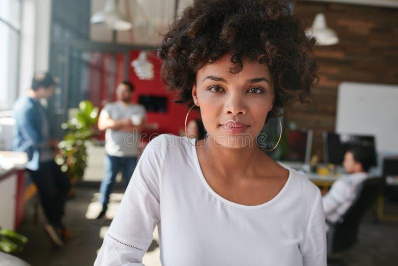 Überzeugter junger weiblicher Designer, der in ihrem Büro steht lizenzfreies stockfoto