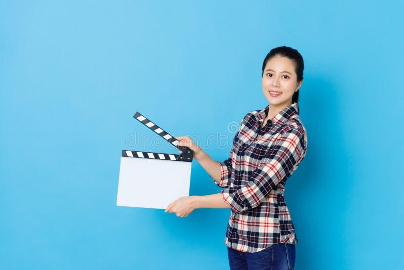 Überzeugter junger weiblicher Direktor, der clapperboard verwendet lizenzfreies stockfoto