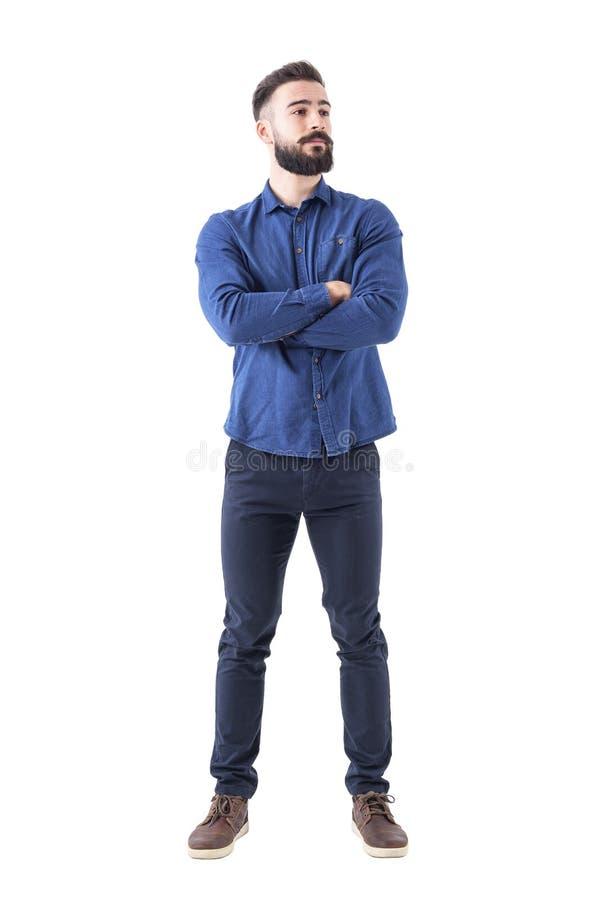 Überzeugter kühler junger bärtiger Mann, der weg mit den gekreuzten Händen steht und schaut lizenzfreie stockfotos