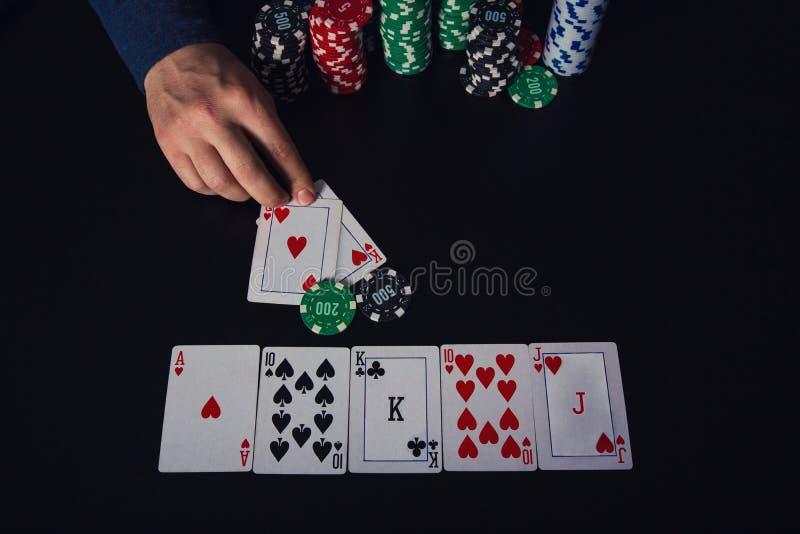 Überzeugter Kerlpokerspieler, der seiner Bank einen großen Stapel Chips, gewinnend am Kasinospieltisch nimmt, der Royal Flush-Kar lizenzfreies stockfoto