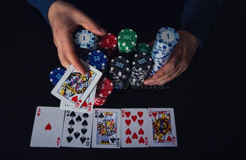 Überzeugter Kerlpokerspieler, der seiner Bank einen großen Stapel Chips, gewinnend am Kasinospieltisch nimmt, der Royal Flush-Kar stockbild
