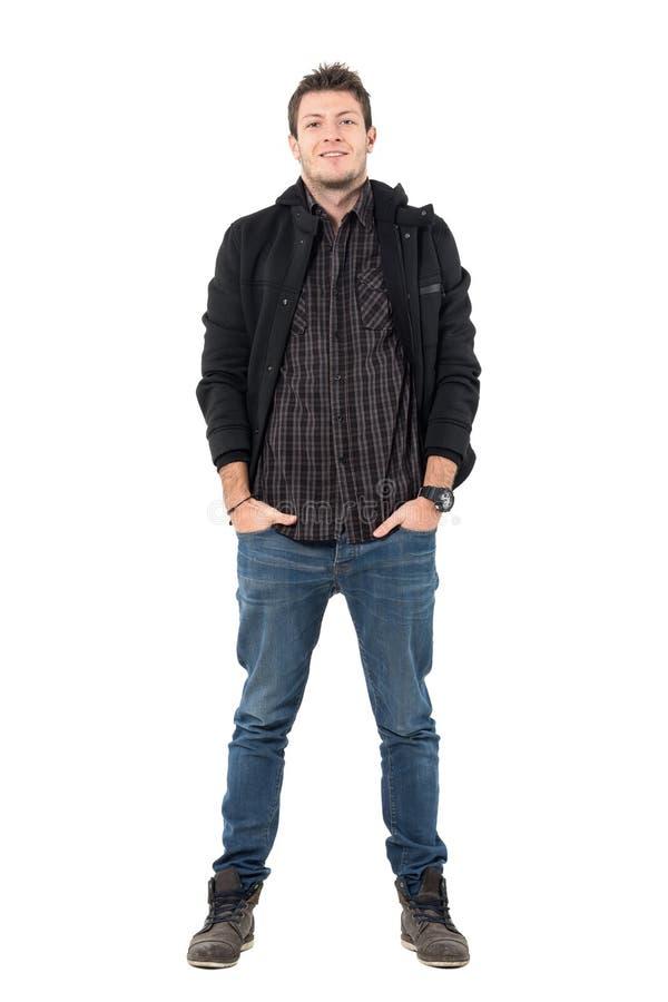 Überzeugter lächelnder entspannter Mann in der schwarzen Jacke und in den Halbstiefeln mit den Händen in den Taschen lizenzfreie stockfotos