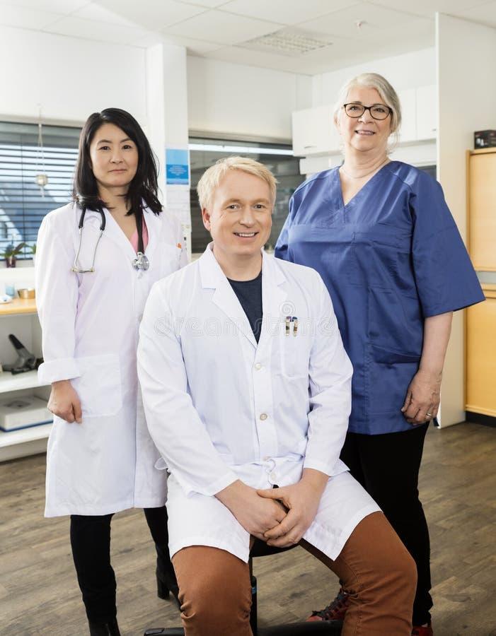 Überzeugter männlicher Doktor Sitting By Team In Clinic lizenzfreie stockbilder
