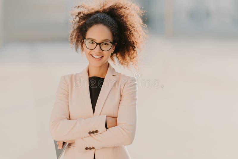 Überzeugter netter weiblicher Unternehmer mit dem gelockten Afrohaar, hält Arme gefaltet, benutzt modernen Tablet-Computer, läche stockfotografie