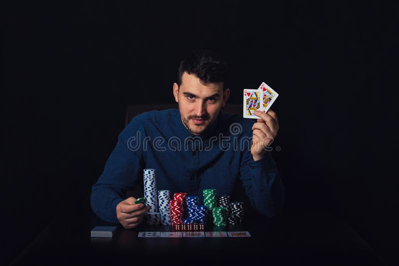 Überzeugter Pokerspieler gesetzt am Kasinotisch, der seine gewinnenden Karten über schwarzem Hintergrund zeigt Spielender Turnier stockbilder