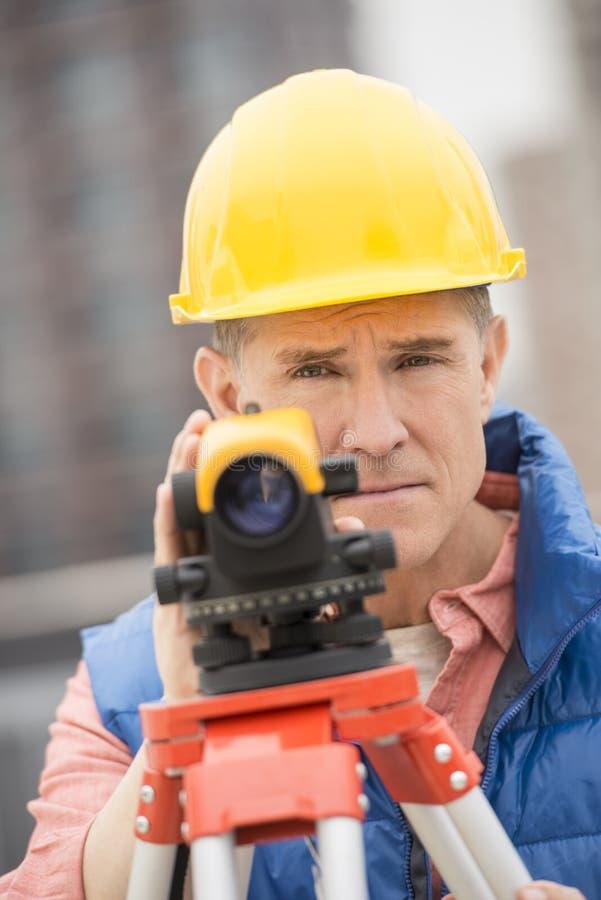 Überzeugter reifer Bauarbeiter With Theodolite lizenzfreies stockbild