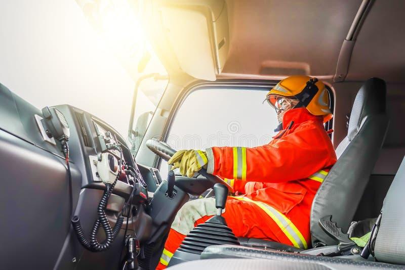 Überzeugter reifer Feuerwehrmann, der Löschfahrzeug mit Kommunikationsinnenansicht an der Station fährt lizenzfreie stockfotografie