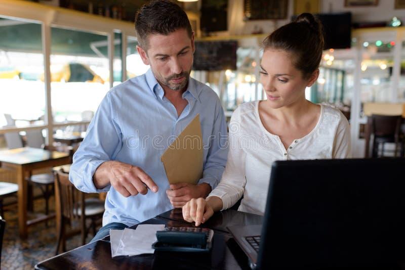 Überzeugter Restaurantmanager, der neuen Angestellten unterstützt lizenzfreie stockbilder