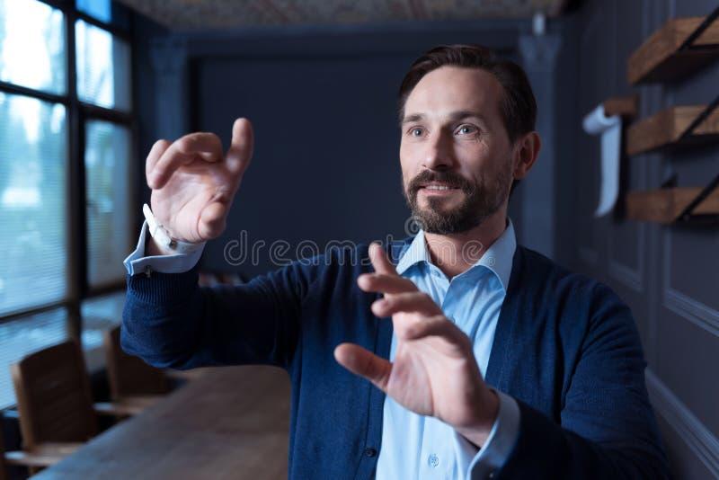 Überzeugter schöner Mann, der mit modernen technologischen Geräten arbeitet stockfotos