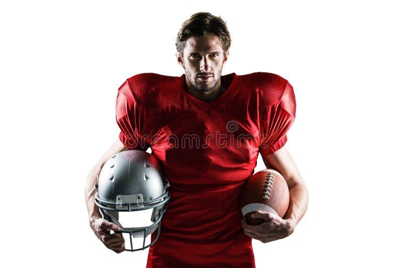 Überzeugter Spieler des amerikanischen Fußballs im roten Trikot, das Sturzhelm und Ball hält stockfotos