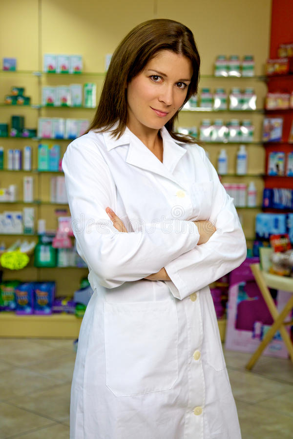 Überzeugter und ernster weiblicher stnading und lächelnder Apotheker stockfotos