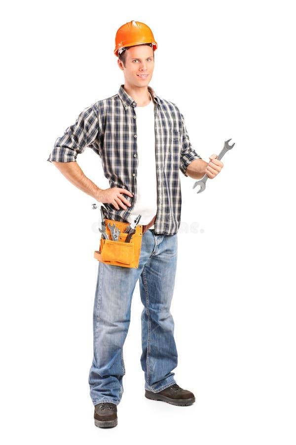 Überzeugter und lächelnder Heimwerker, der einen Schlüssel anhält stockfoto