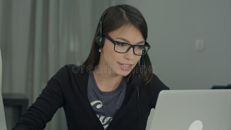 Überzeugter und schöner Kundenbetreuungsbetreiber, der in Call-Center arbeitet lizenzfreie stockbilder