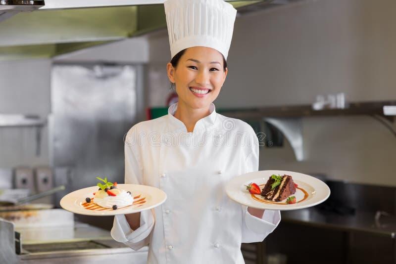 Überzeugter weiblicher Chef, der gekochtes Essen in der Küche hält stockbilder