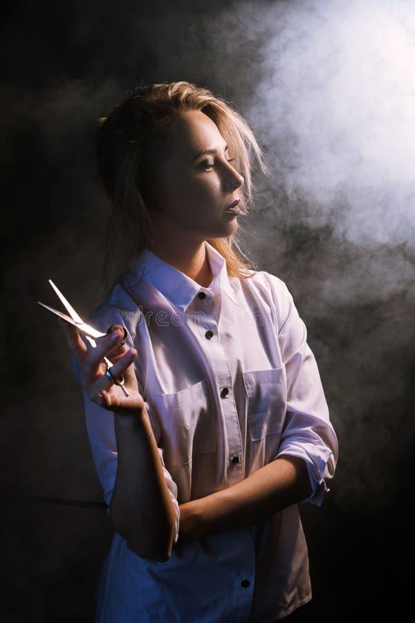 Überzeugter weiblicher Friseur auf schwarzem Hintergrund stockbild