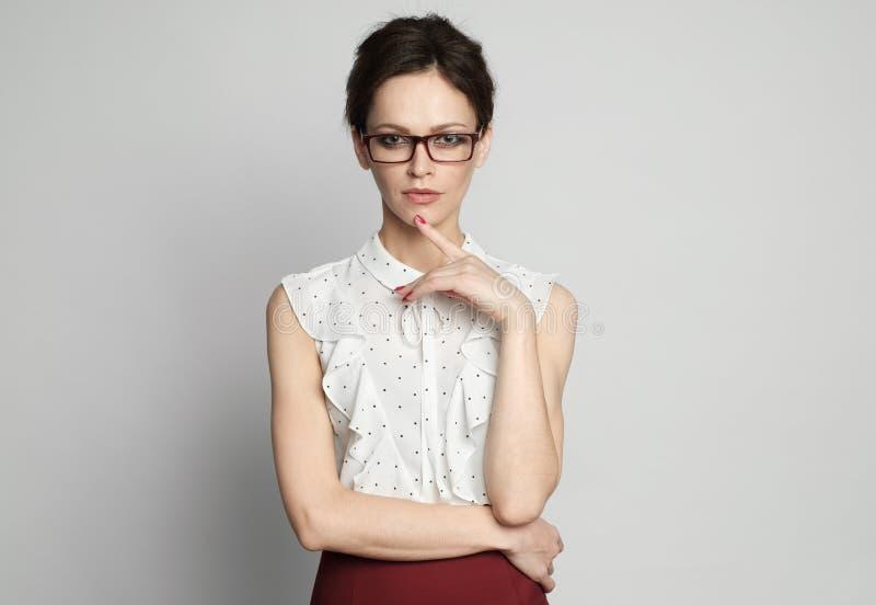 Überzeugter weiblicher Lehrer beim Glasdenken stockfotografie