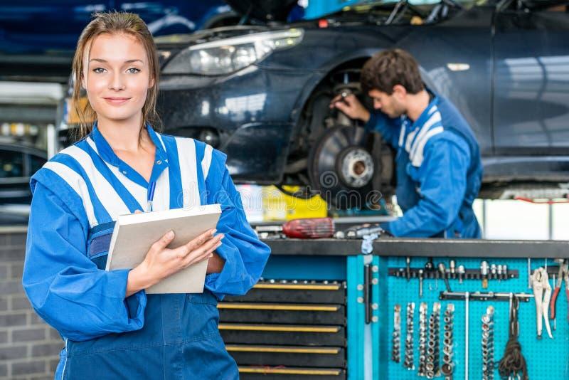 Überzeugter weiblicher Mechaniker With Maintenance Checklist an der Garage stockfotografie