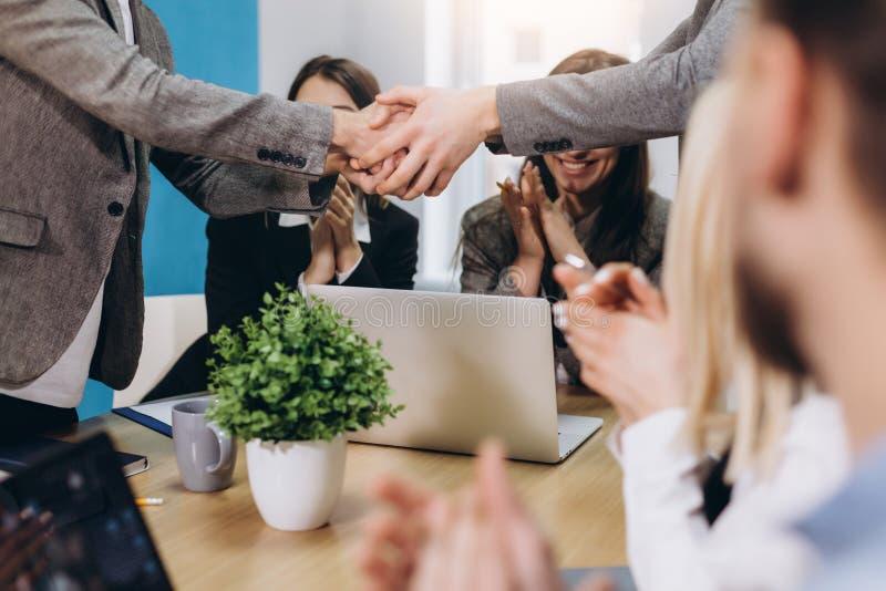 Überzeugter zwei Geschäftsmann, der Hände während einer Sitzung im Büro, Erfolg, Behandeln, grüßend rüttelt stockfoto
